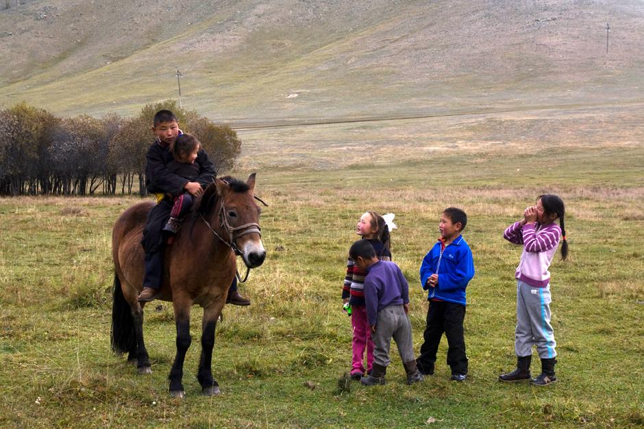 Mongolskie dzieci spotylają się z podróżnikami