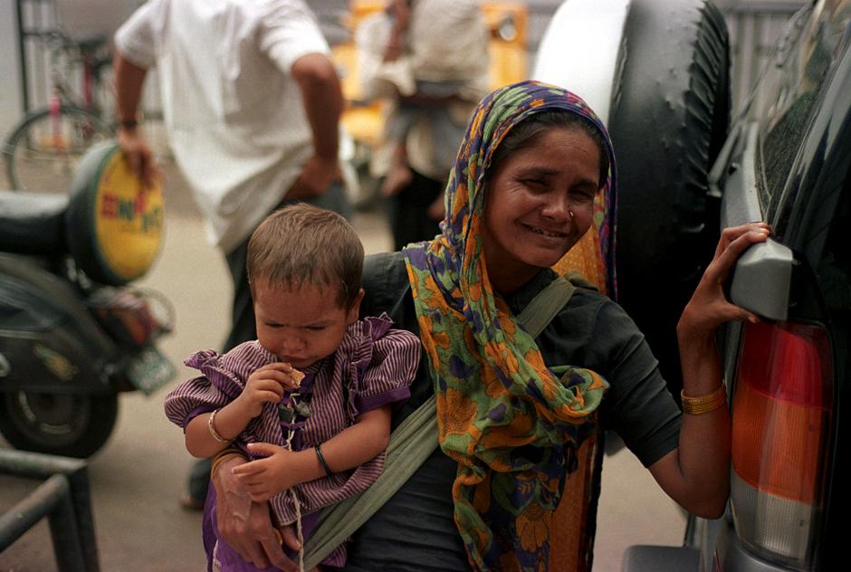 Indie, Delhi. Żebrząca matka z dzieckiem na rękach.