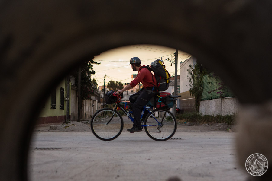 Todd Tumolo pedals past a discarded tire in Cholula