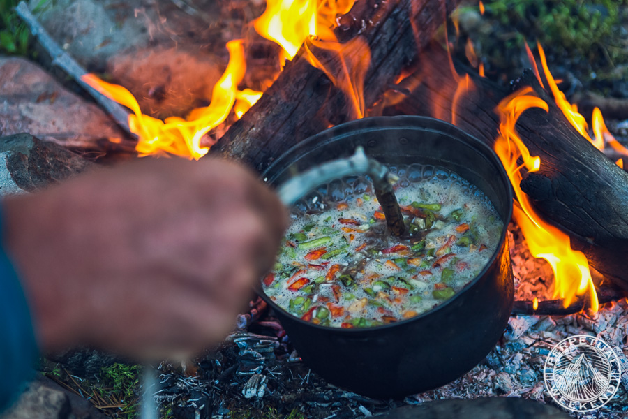 Forrest stirs the cook pot with a stick
