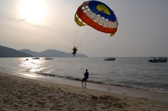 Practicando el parasailing en Batu Ferringhi, isla de Penang, Malasia