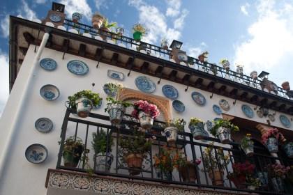 Una casa decorada con platos, macetas, plantas y flores, en Granada, España