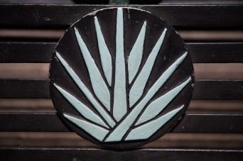 Escudo de agave en una banca de la plaza central de Tequila, México