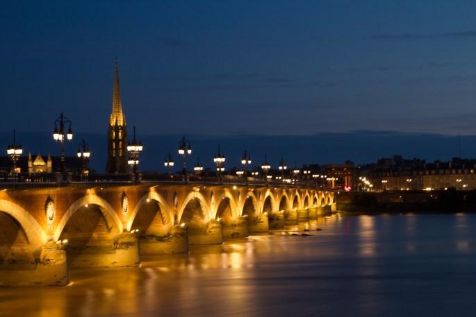 Vista nocturna del puente de piedra y la Basílica de San Miguel, Burdeos, Francia