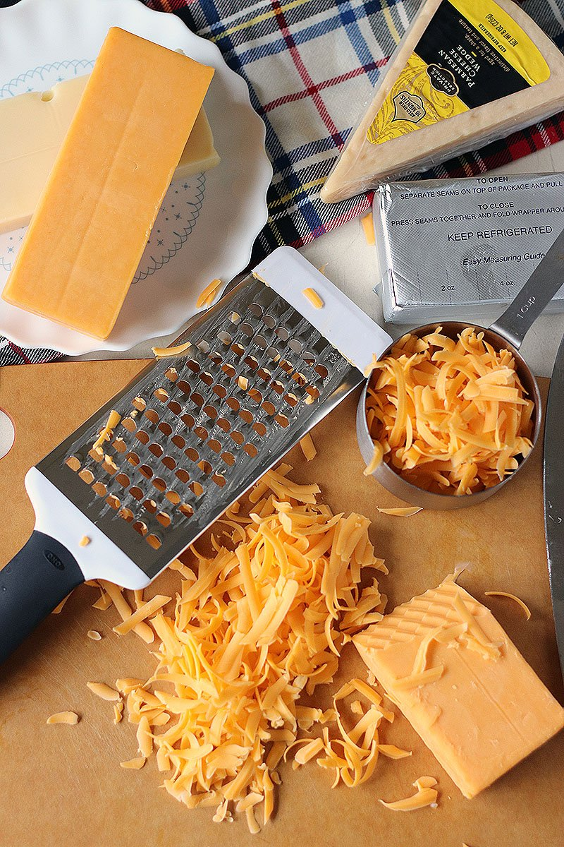 grater and cheese on cutting board for homemade baked mac and cheese