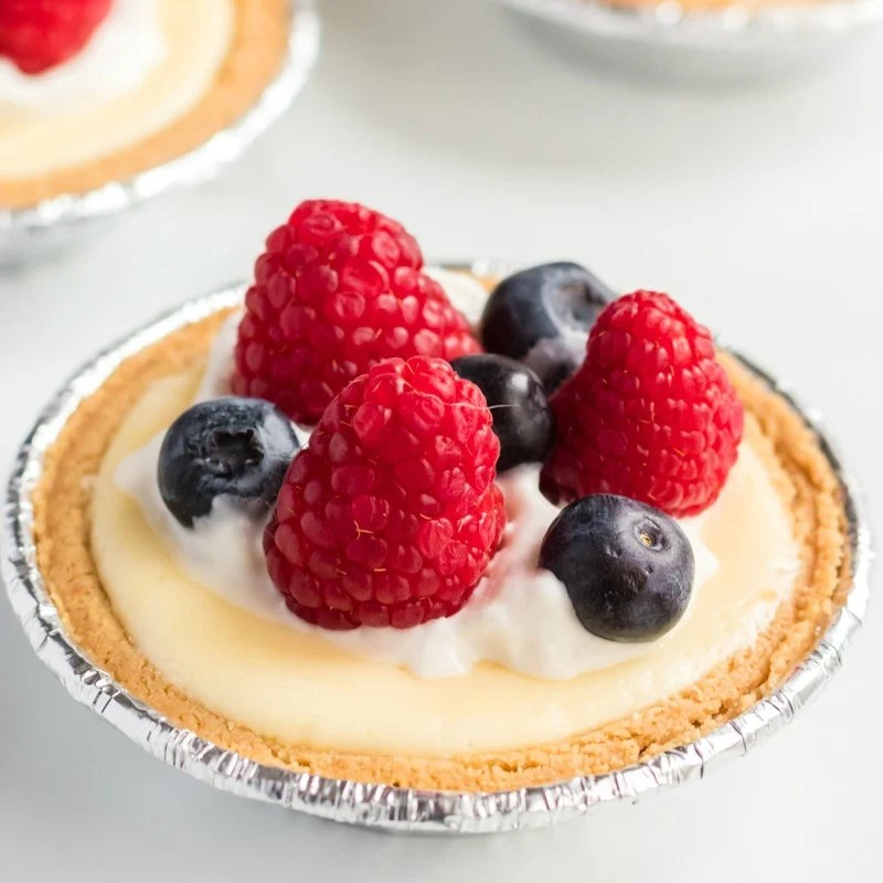 single mini cheesecake topped with raspberries & blueberries