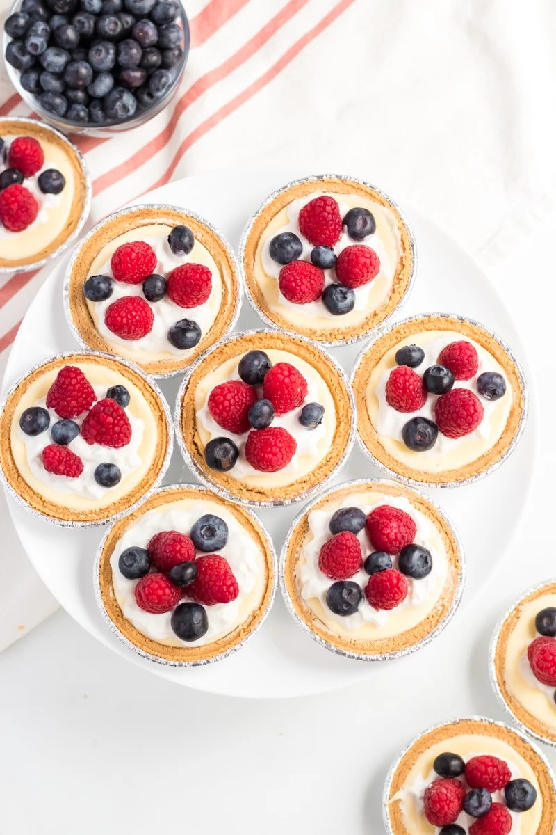 mini cheesecakes on a platter topped with berries