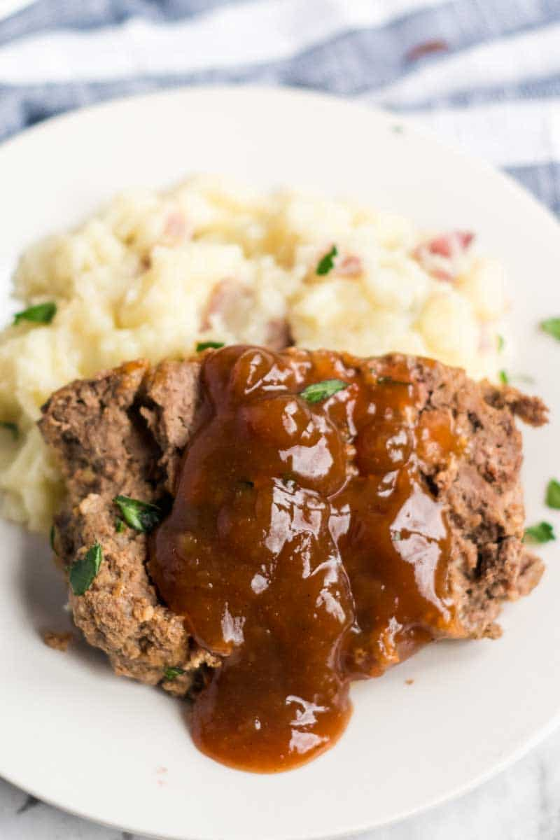 meatloaf with brown gravy on a white plate with mashed potatoes