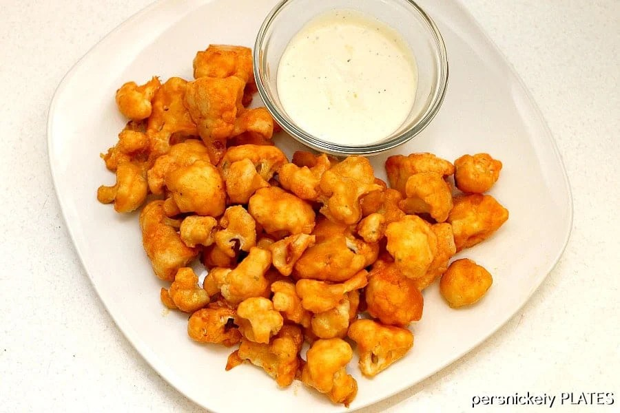 cauliflower buffalo wings on white plate with ranch cup