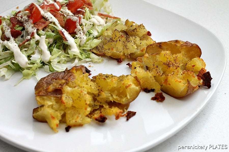 crash hot potatoes on a white plate with a side salad