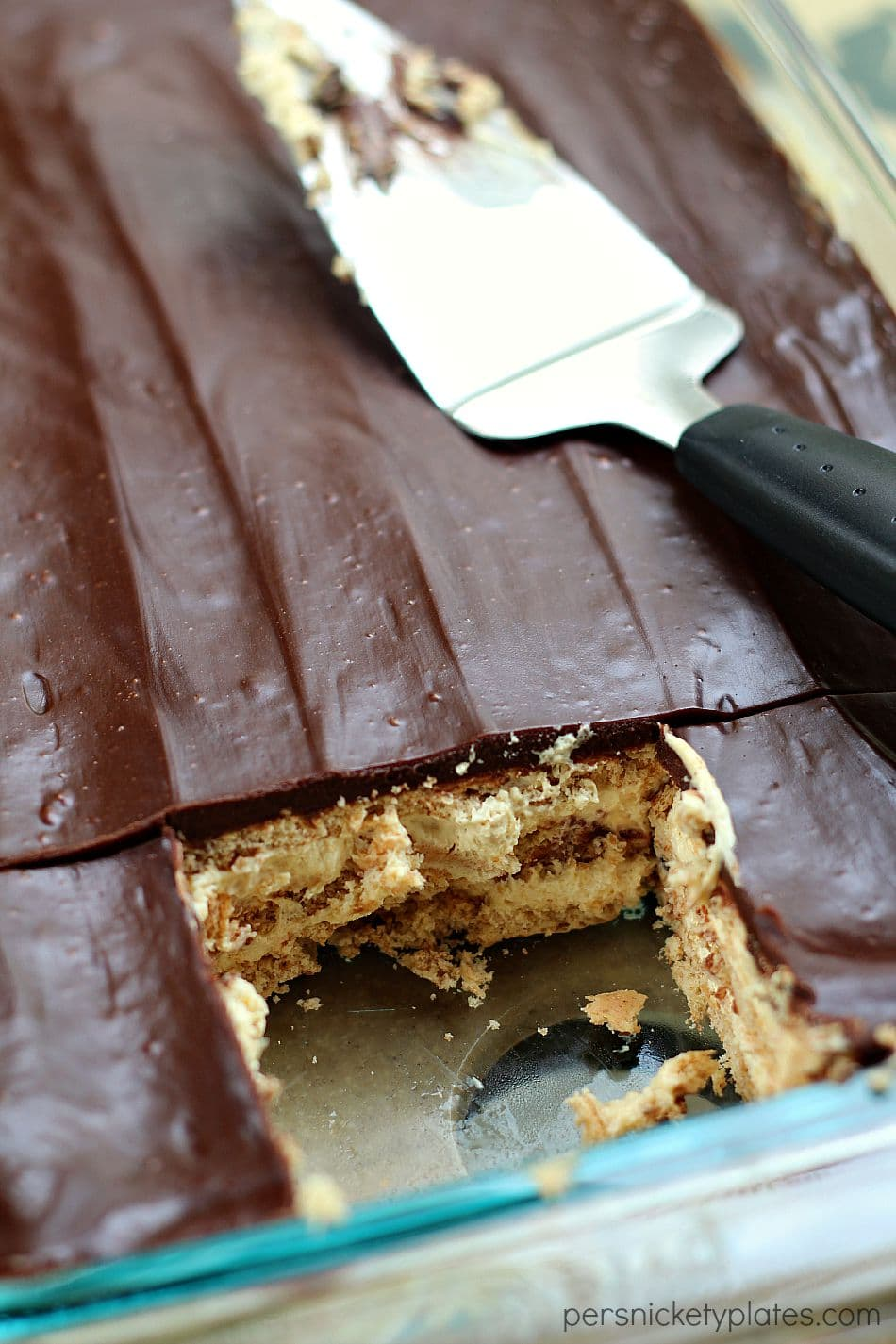 pan of chocolate peanut butter eclair dessert in baking dish with serving spoon
