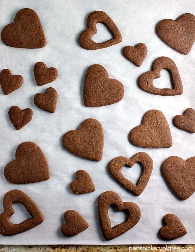 Chocolate Frosted Valentine Cookies start with a simple chocolate roll-out cookie base, frosted and sprinkled for Valentine's Day! | www.persnicketyplates.com