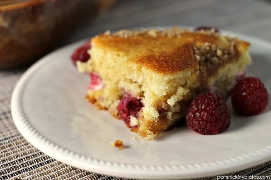 A layer of cake, a layer of raspberries and cream cheese, and a crumb topping come together perfectly in this Raspberry Cream Cheese Coffee Cake. Perfect for Mother's Day!   Persnickety Plates