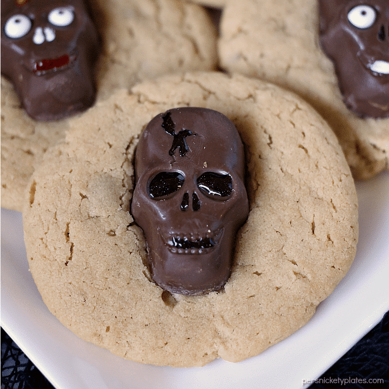 Peanut Butter Butterfinger Skull Cookies start with a soft and chewy from scratch peanut butter cookie then are topped with a spooky, decorated Butterfinger Peanut Butter Skull Cup. Perfect for any Halloween party! | www.persnicketyplates.com