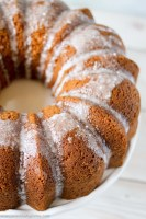 angled shot of butterscotch bundt cake with powdered sugar glaze