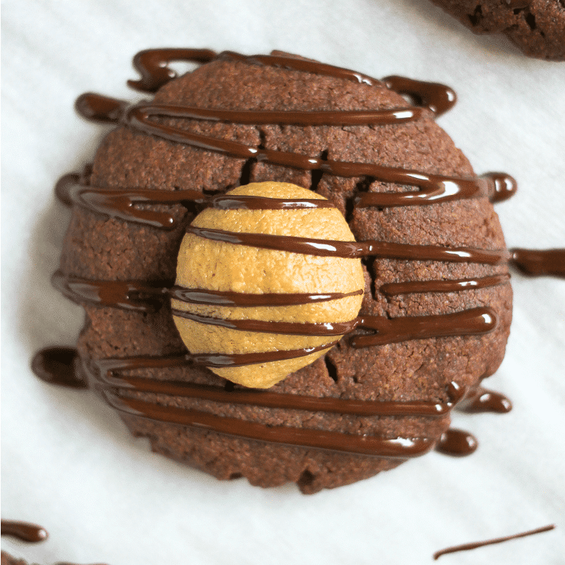 close up of chocolate cookie filled with peanut butter and drizzled with chocolate