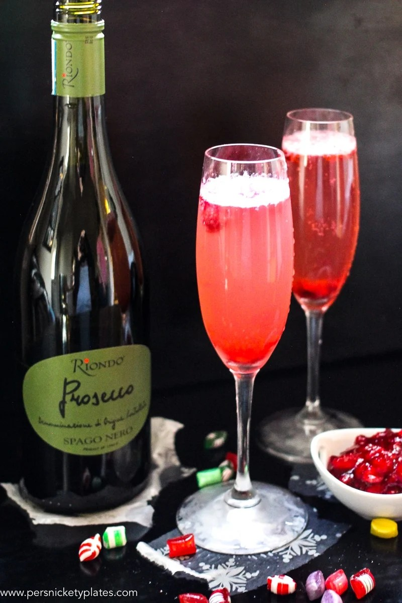 This Cranberry Prosecco Spritzer combines the vibrant bubbles of Riondo Prosecco with the warm winter notes of spearmint and cranberries. It's the perfect accompaniment to wrapping gifts and spending time with family and friends around the fire or in the kitchen. | www.persnicketyplates.com
