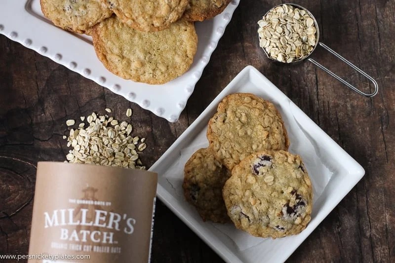 two white square plates of ranger cookies with spilled miller's oats and measuring cup