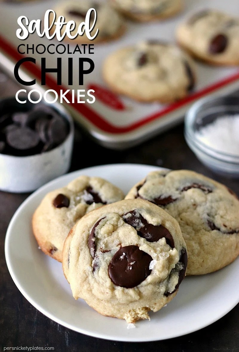 three Salted Chocolate Chip Cookies on a white plate with extras on a baking sheet