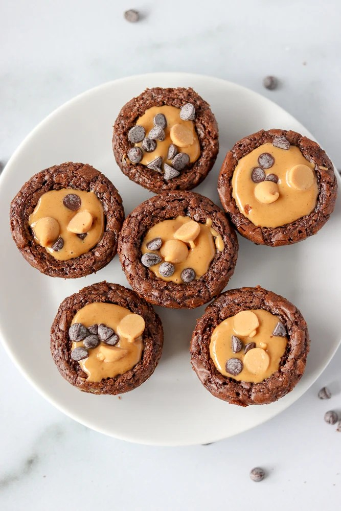five brownie bites topped with peanut butter on a white plate