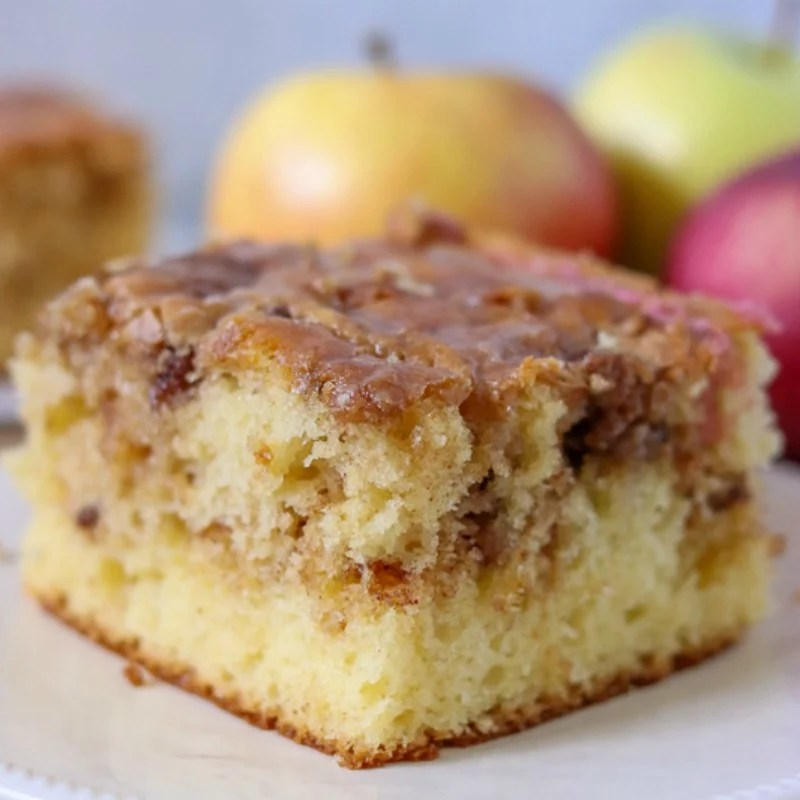 close up of slice of honey bun cake on white plate