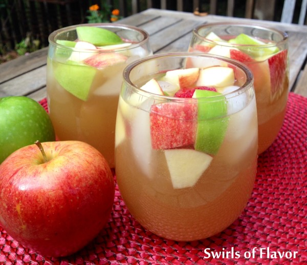 three apple cider sangrias sitting next to an apple