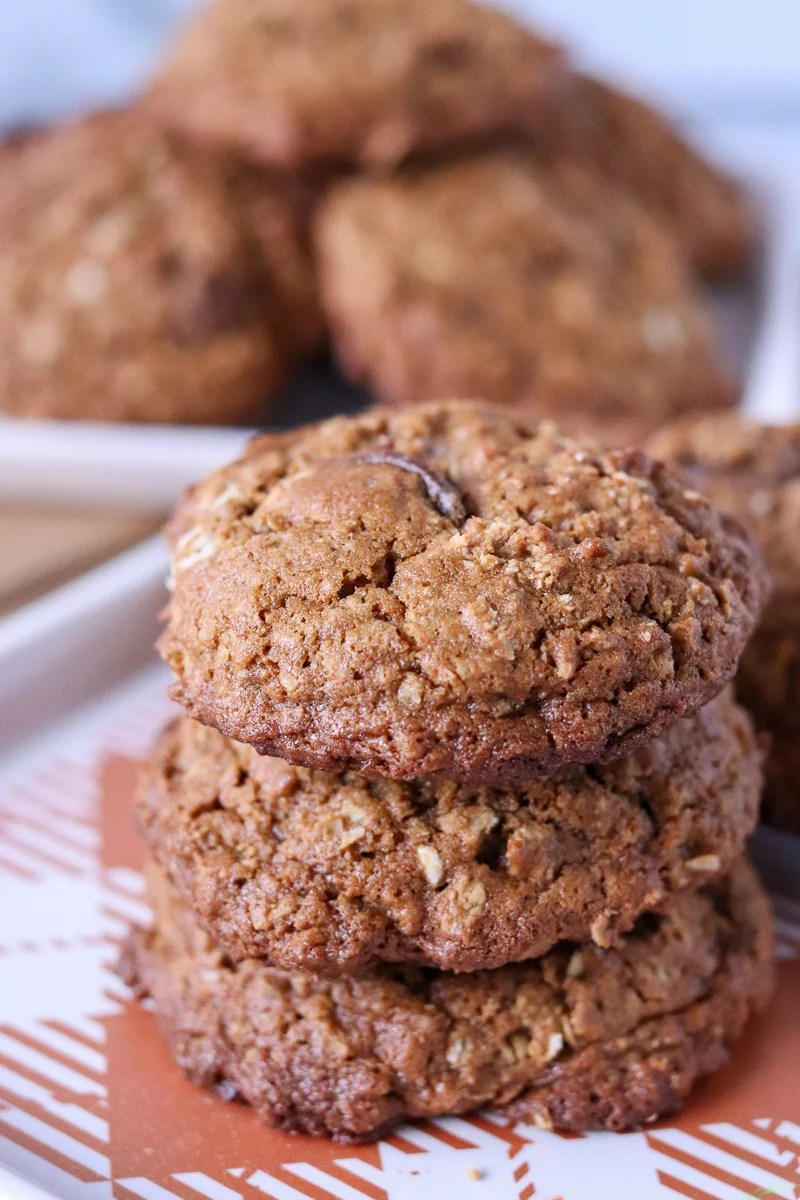 stack of molasses cookies with plate in the back