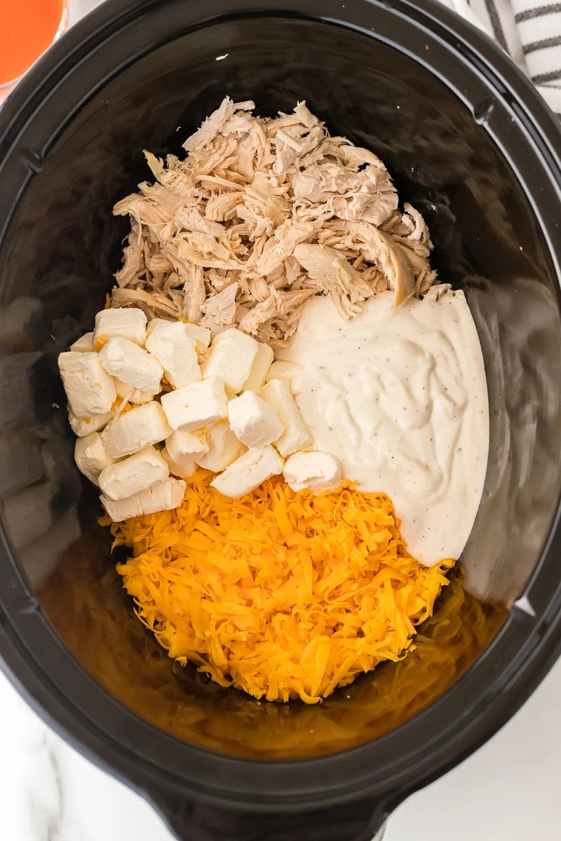 overhead shot of slow cooker bowl of buffalo chicken dip ingredients