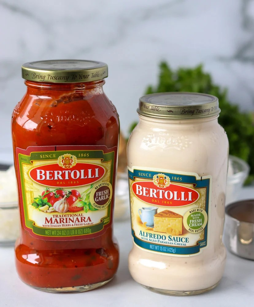 two jars of bertolli marinara and alfredo sauce