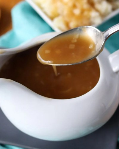 spoon with gravy over a gravy boat