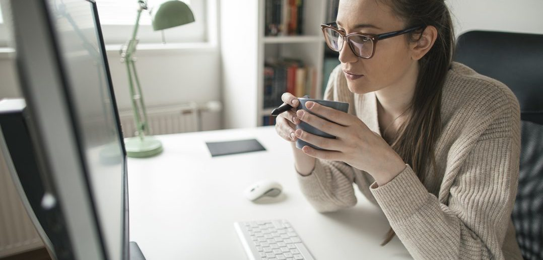 Women working on computer. Working from home. Drinking hot drink