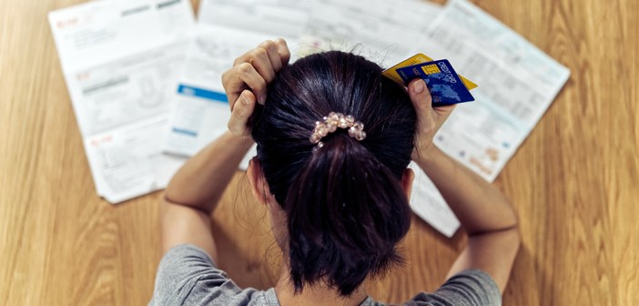 women holding her head and credit cards. stressed from debt