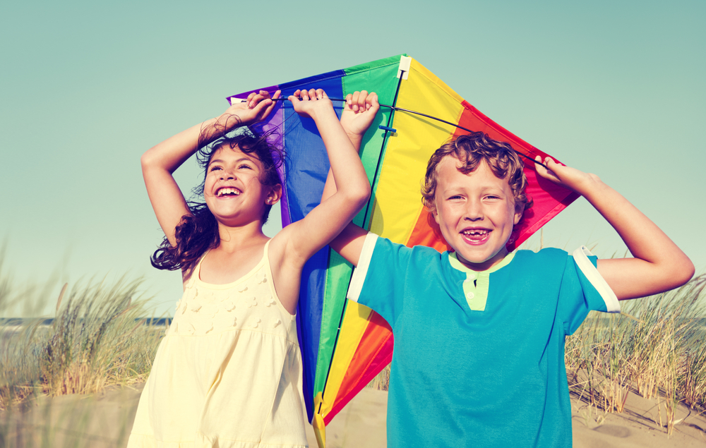 A healthy little girl and boy play with a rainbow-colored kite.