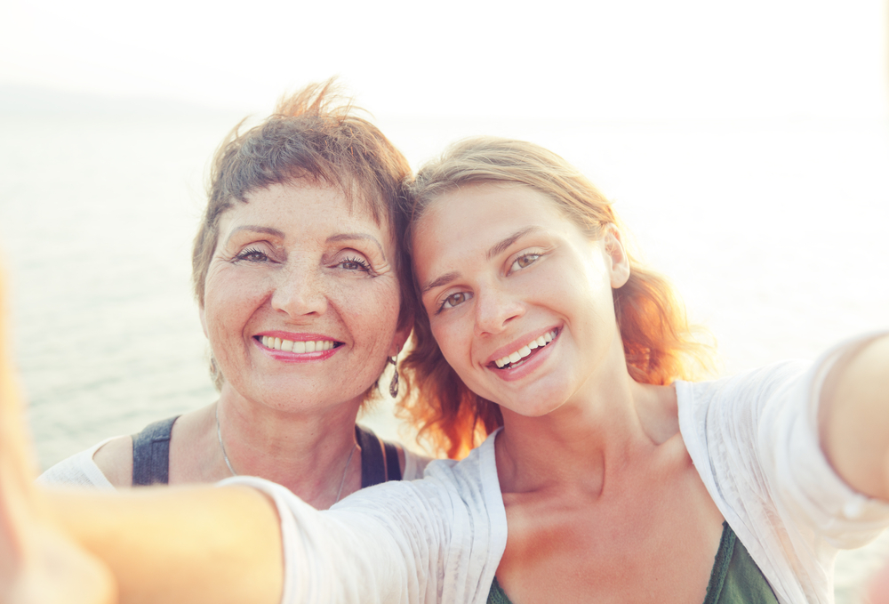 A mom and daughter snap a selfie of themselves at the beach.