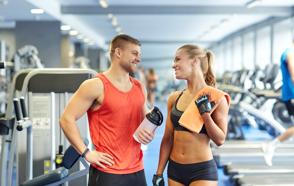 A gym rat tells a girl how she should be drinking protein shakes. She thinks Personal Trainer Food is better.
