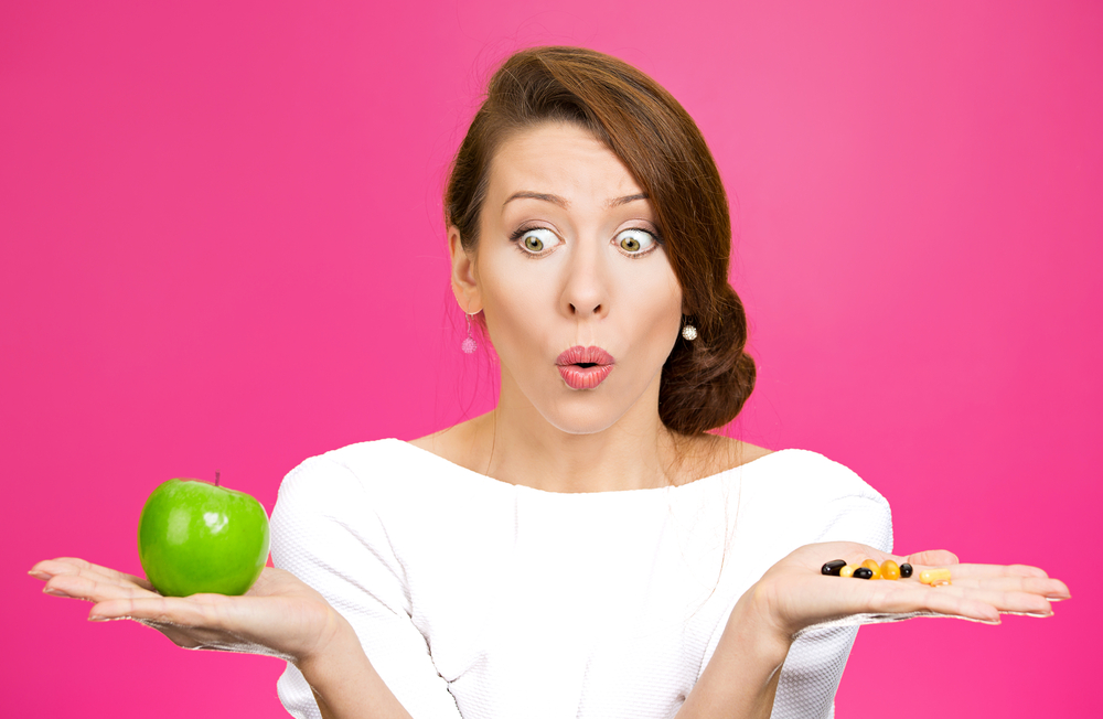 A woman is confused by the noise of commercials. Should she eat the apple or take the diet pills?
