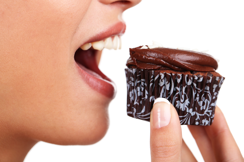 A woman poised to eat a chocolate cupcake to satisfy a craving.