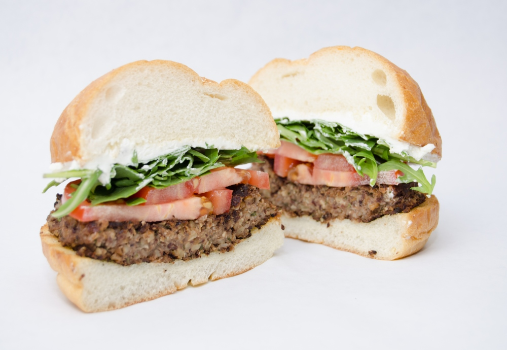 A vegetarian burger with tomatoes, lettuce, and mayonnaise on a fluffy white bun.