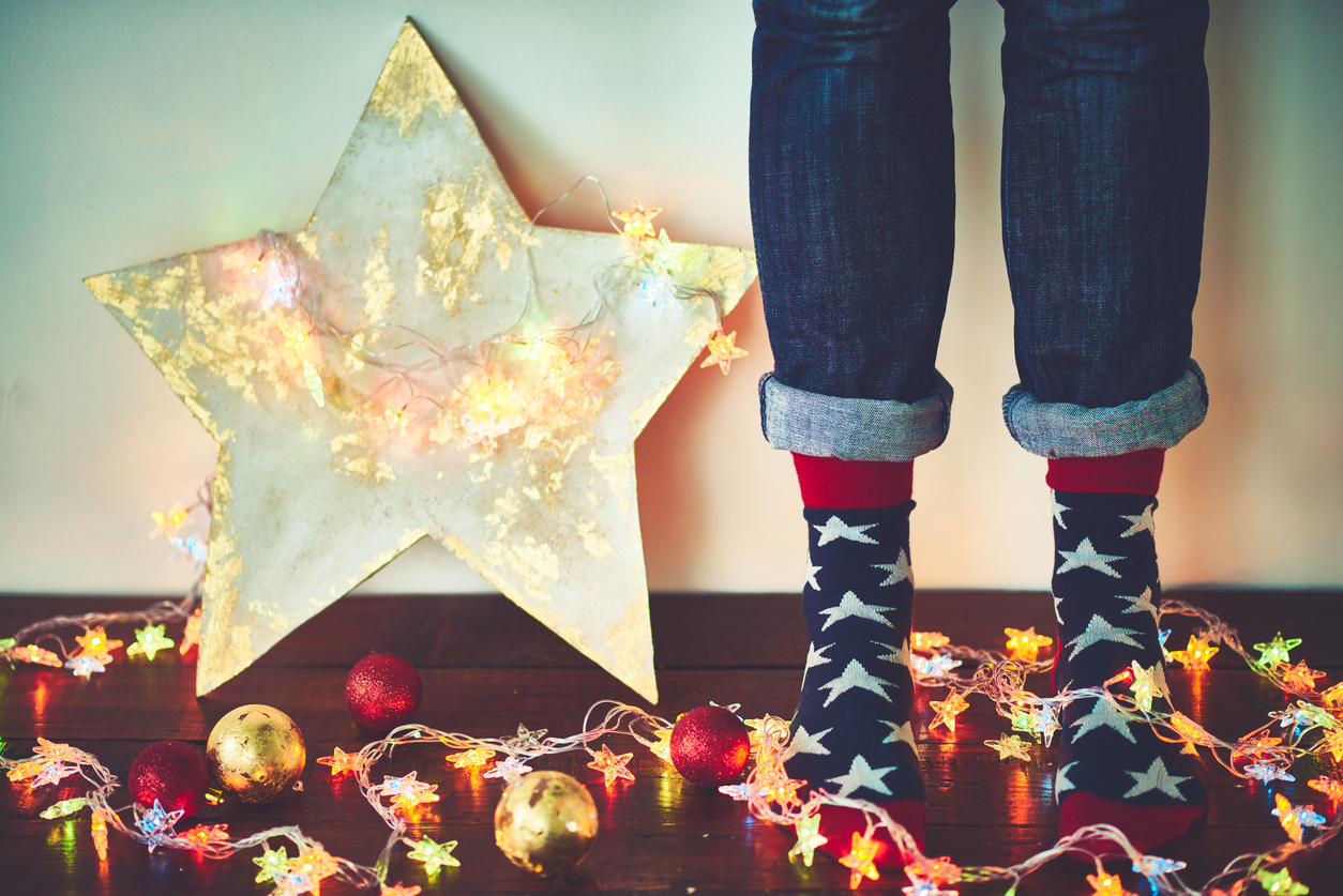 Human feet in socks with foam stars, plywood star, Christmas lights and ornaments on hardwood floor.