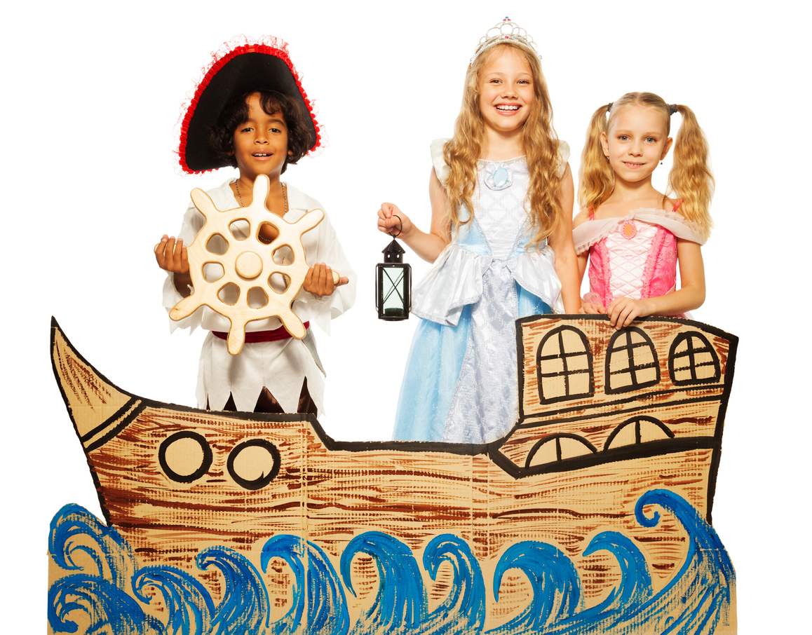 Theatrical play boy in costume of pirate and girls in princess dress sail on cardboard ship.
