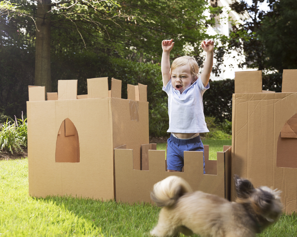 A little boy plays in a castle made from cardboard boxes.