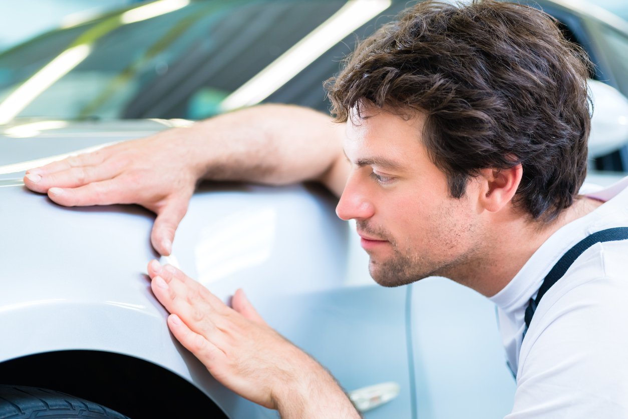 Male mechanic examine car finish on dents or scratches in workshop.