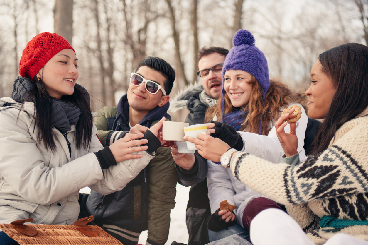 Group of millenial young adult friends enjoying wintertime and in a snow filled park.