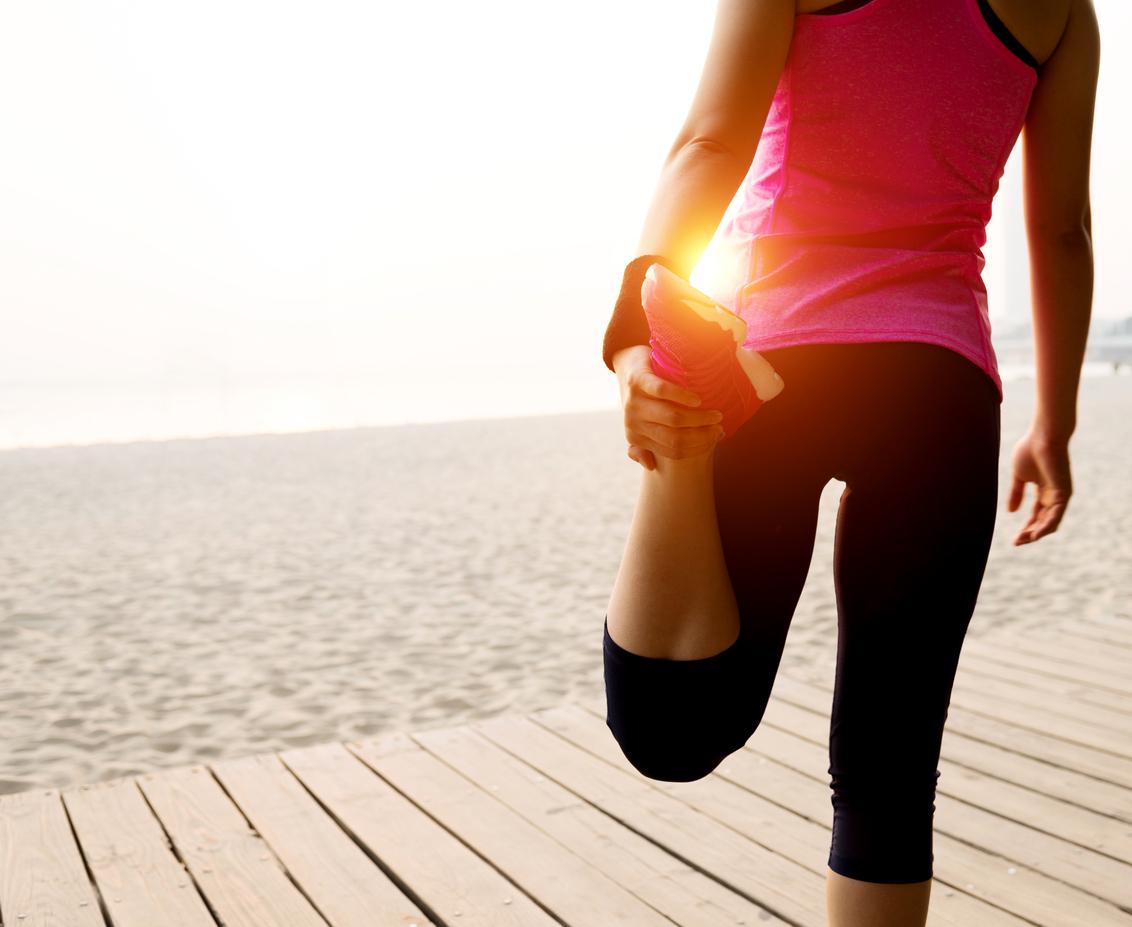 Female runner stretching before run at beach.