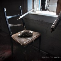 Lucy - A lonely chair looks out a broken window.