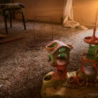 Shattered Palace - A child's toy palace sits amongst broken glass and debris.