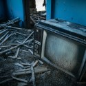 Think Outside the Box - Vintage television overturned in a crumbling house.
