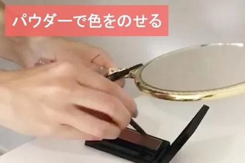 眉パウダーをブラシに取る玉村麻衣子さんの手元