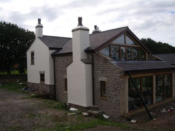 Old farmhouse with large rear two story stone extension with bi folding doors.