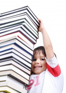 A big tower of many books vertical and kid reaching a top